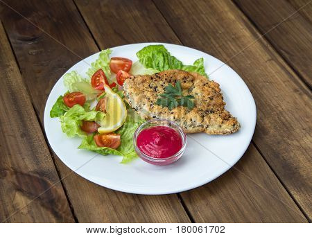 Homemade Breaded Schnitzel with salad and berry sauce on old wooden table