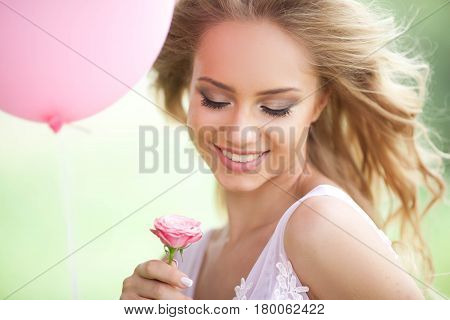 Embarrassed beautiful young girl with tender rose flower in hands on nature background