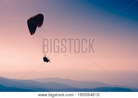 Silhouette of flying paraglide in a sky above the mountain valley.