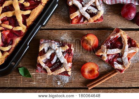 Sand cake with plums on a wooden background with space for text