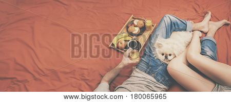 Young couple is lying in bed with dog and having a healthy breakfast.