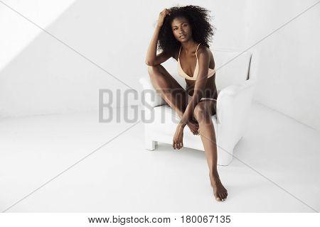 Stunning bikini babe posing in armchair portrait
