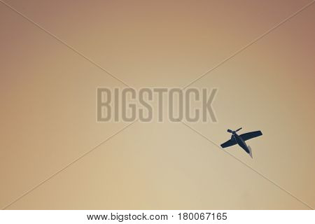 Small wooden toy plane flies in the sky creative background
