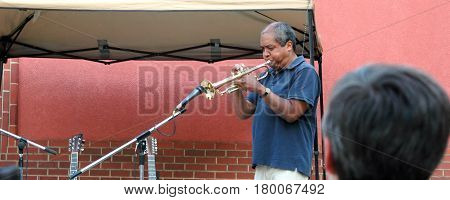 African american jazz trumpet player performing outdoors.
