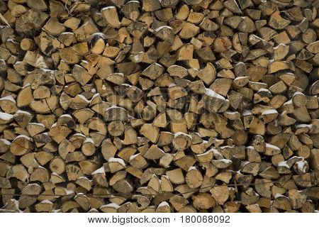 wall firewood background of chopped logs in a pile