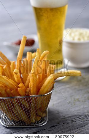 closeup of some appetizing french fries served in a metal basket on a gray rustic wooden table and a glass with beer and some bowls with mayonnaise and ketchup in the background