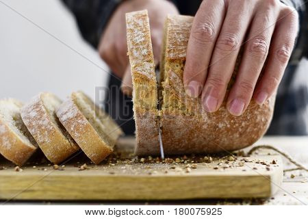 closeup of a young caucasian man cutting a loaf of bread in slices with a knife