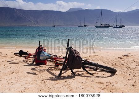 a pair of bicycles on the white sand of La Francesa Beach in La Graciosa island, in the Canary Islands, Spain, with the Famara massif of Lanzarote island in the background