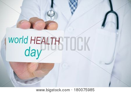 closeup of a young caucasian doctor man showing a signboard with the text world health day