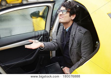 Portrait of young Middle - Eastern businessman getting out of taxi to rainy autumn street, looking displeased and testing rain with hand