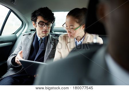 Portrait of two successful business people riding on backseat of car: man and woman discussing work documents in taxi