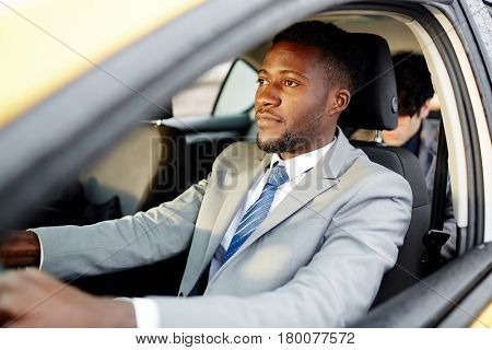 Portrait of successful African- American businessman driving car and focused on the road