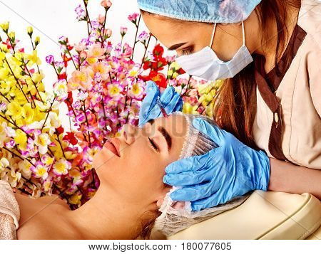 Filler injection for female forehead face. Plastic aesthetic facial surgery in beauty clinic. Woman giving injections. Doctor in medical gloves and hat with syringe on spring flowers background.