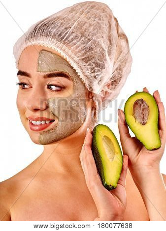 Avocado clay face mask. Woman in medical hat holding half of green fruit with stones isolated background. Facial beautiful procedure concept.