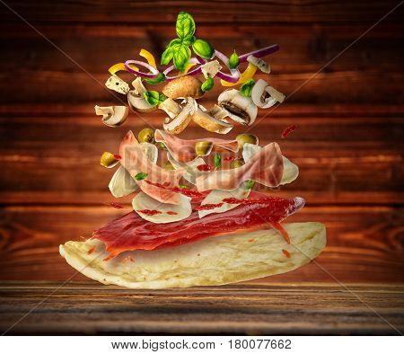 Concept of flying ingredients with pizza dough, placed on wooden planks background. Food preparation, fresh meal ready for cooking