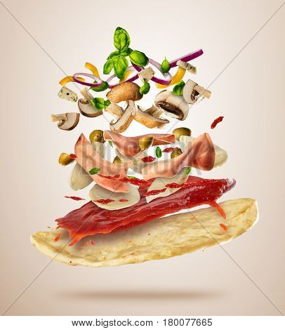 Concept of flying ingredients with pizza dough, isolated on bright background. Food preparation, fresh meal ready for cooking