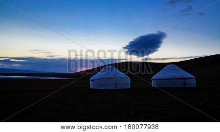 Cloud over the yurts at the shore of Song Kol Lake at the dawn Kyrgyzstan