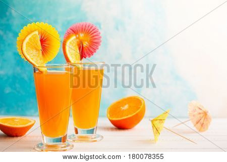 Fresh summer tropical cocktail with slice of orange,  drinking straw and cocktail umbrellas on white wooden table. Against turquoise background.  Place for your text.
