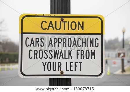 A caution cars approaching crosswalk from your left sign