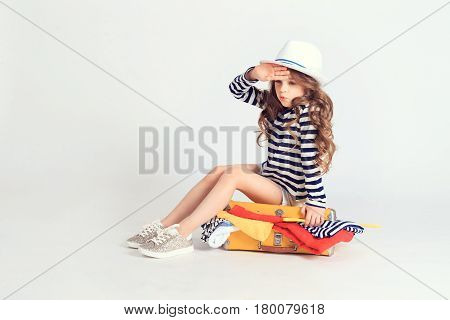 Small tired girl has finished packing her suitcase and sitting on it trying to lock it. A picture is taken at studio and has white background