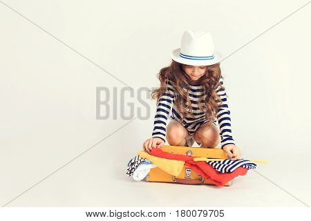 Young girl is trying persistently to close up overloaded with her clothes suitcase. The picture is taken at studio and has white background