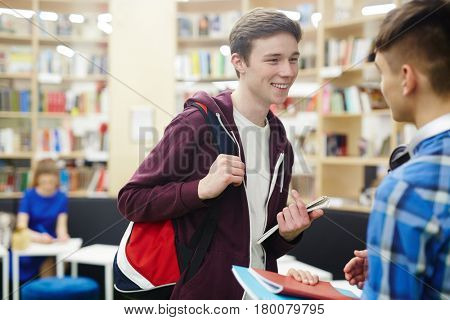 Portrait of smiling teenage boy talking to friend in college library, discussing schoolwork