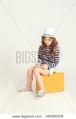 A serious young girl is writing something in her notebook and sitting on a yellow suitcase. The picture is taken at studio and has white background.