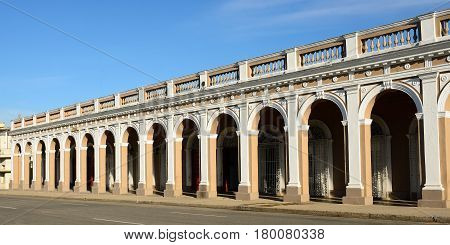 Colonial building with arcades by the main square (Plaza de Armas) in the Cienfuegos city on Cuba