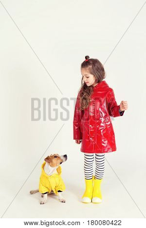Pretty girl in red raincoat and rubber boots is standing with her dog Jack-Rassel terrier which is wearing yellow raincoat. Kid holding in hand something invisible. hildhood, fashion, imagination, friendship concept
