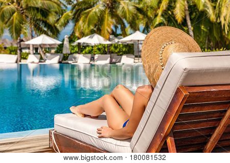 Woman relaxing in lounger at the poolside