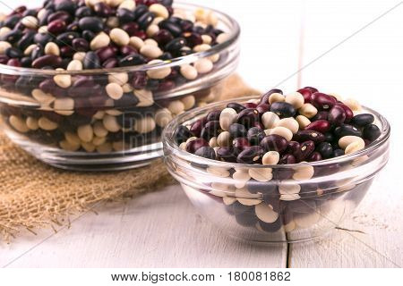 Coloreful haricot bean on the glass plate and burlap on white wooden table