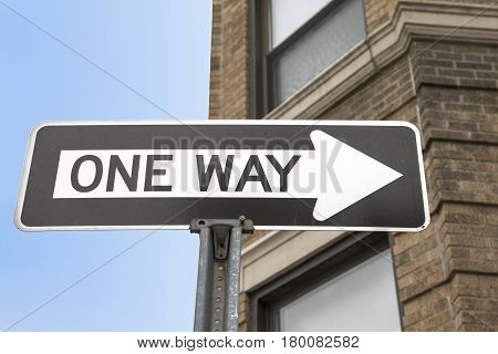 A black and white one way arrow sign