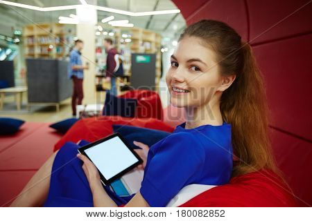 Portrait of beautiful blond girl resting on bean bag in creative workspace of modern college, using tablet with blank screen and looking at camera smiling