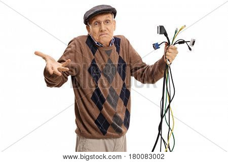 Baffled senior holding different types of electronic cables and looking at the camera isolated on white background