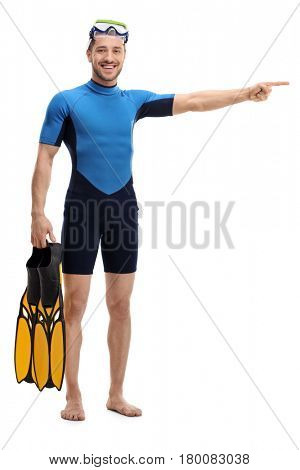 Full length portrait of a man in a wetsuit with snorkeling equipment pointing right isolated on white background