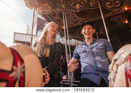 Smiling Friends On Amusement Park Carouse