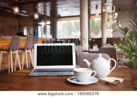 Open net-book and cup of tea with lemon on table in moder cafe / restaurant / bar interior. Laptop computer with blank copy space for your text message or promotional content freelance remote job during tea break