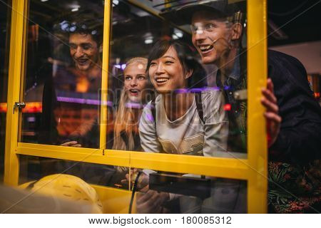 Friends Playing Toy Grabbing Game At Amusement Park