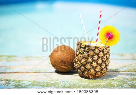 Exotic pineapple cocktail near pool. Pina colada