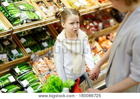 Frowning girl looking at her mother in supermarket
