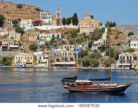 A yacht in a bay on Simi island, Greece with traditional houses on the hill in the background