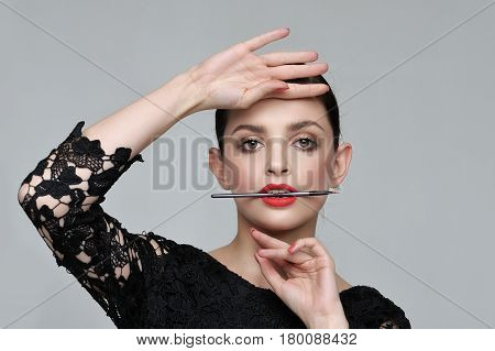 Girl Is Holding A Brush For Cosmetics In Her Teeth In A Slightly Open Mouth