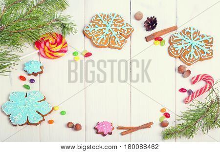 Christmas cookies Christmas trees snowflakes. Christmas Ginger and Honey colorful cookies with fir tree branches on the white wooden background. Top view.