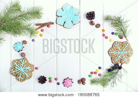 Christmas cookies Christmas trees snowflakes. Christmas Ginger and Honey colorful cookies with fir tree branches on the white wooden background.