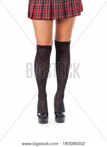Beautiful female legs in short skirt and stockings. Isolated on white background
