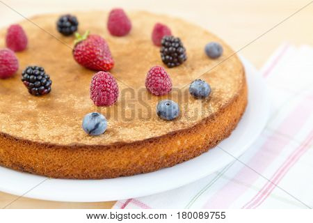 Biscuit cake with berries. Homemade Cake with Fresh Berries. Biscuit cake with fresh raspberries blueberries blackberries strawberries on wooden background.