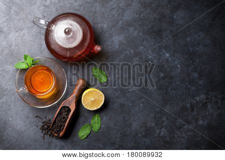 Tea cup, teapot and dry tea in spoon on stone table. Top view with copy space