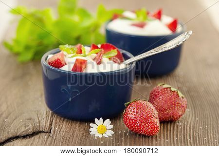 Milk fruit dessert. Whipped cream with strawberries. Serving tasty treats from dairy cream and red strawberries standing on the wooden table. Blue cup with cream and a silver spoon. Berries and cream.
