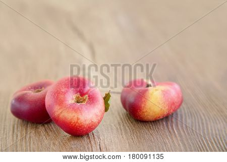 Fig peaches. Fresh flat peaches on wooden background. Selective focus.