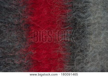 Close-up of black handmade woollen felt blanket with red stripe